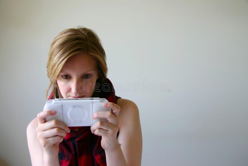 Fille jouant la console tenue dans la main de jeu image libre de droits