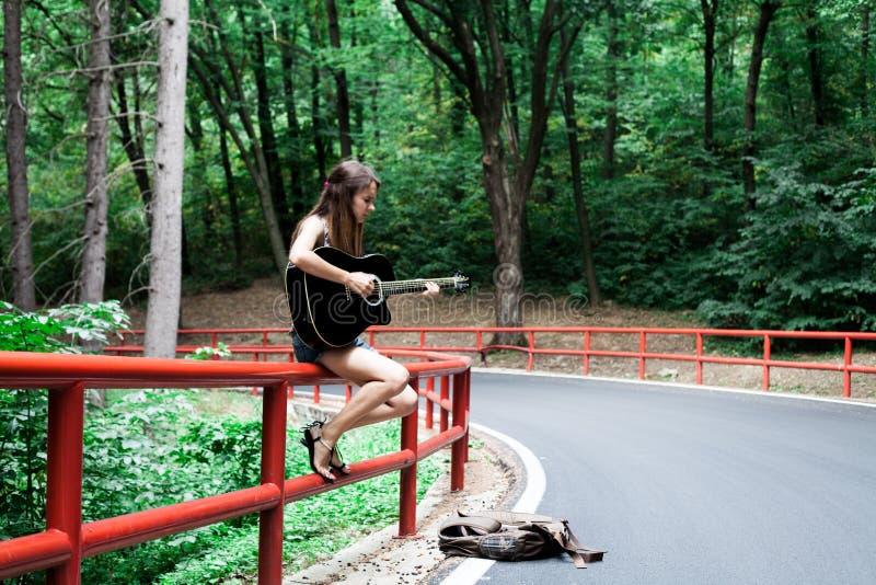 Fille jouant la guitare d'un côté de route image libre de droits