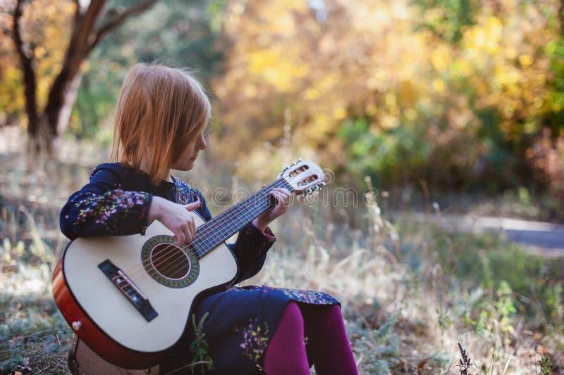 Fille jouant la guitare dans la forêt d'automne images libres de droits