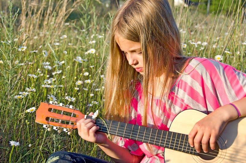 Fille jouant la guitare dans les marguerites sauvages photos libres de droits