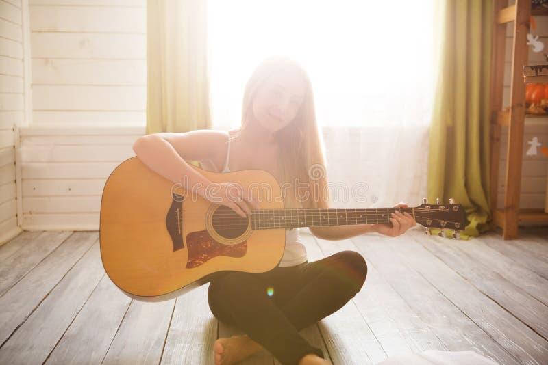 Fille jouant la guitare et le chant Jeune femme avec de longs cheveux étudiant la musique à la maison Femme s'asseyant sur le gui photographie stock libre de droits