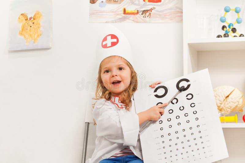 Fille jouant le docteur avec le signe et l'indicateur d'oculiste image stock