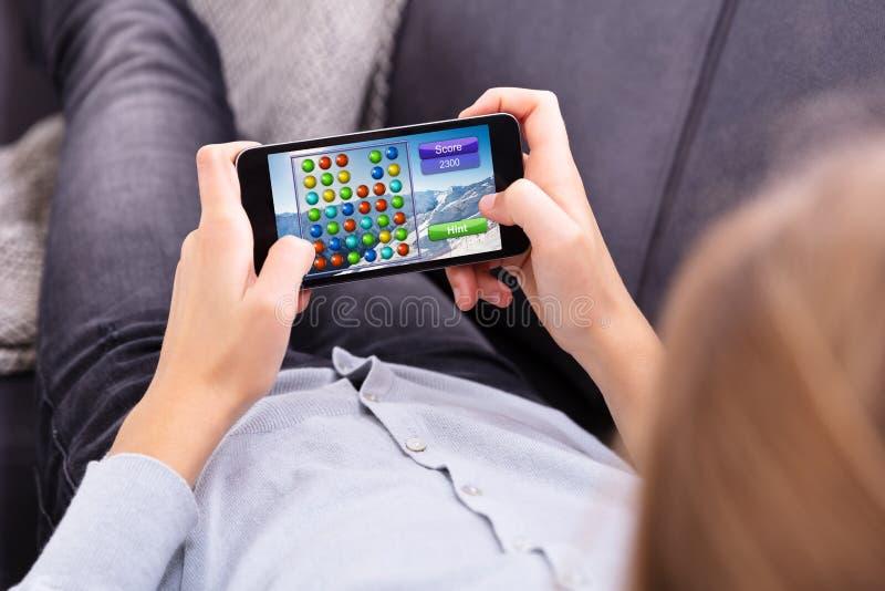 Fille jouant le jeu au t?l?phone portable photo libre de droits
