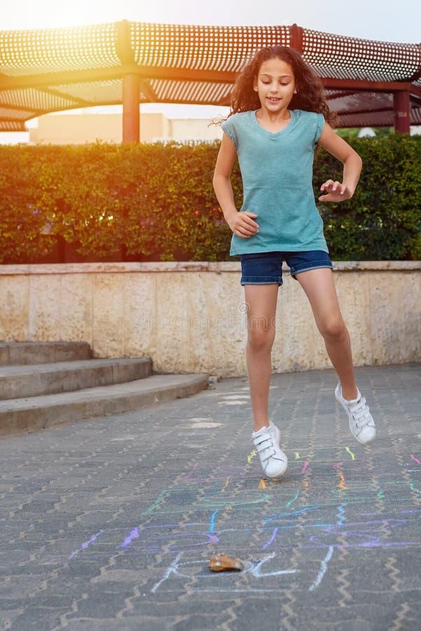 Fille jouant le jeu de jeu de marelle sur l'asphalte sur le terrain de jeu photographie stock libre de droits