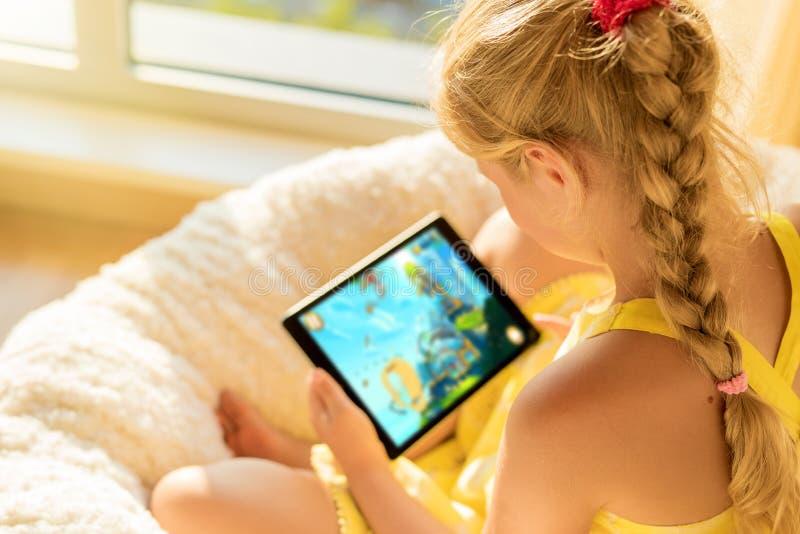 Fille jouant le jeu sur la tablette images stock