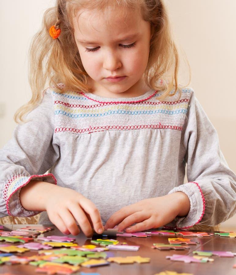 Fille jouant le puzzle photos stock