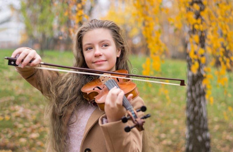 Fille jouant le violon en parc d'automne à un feuillage jaune b photographie stock libre de droits
