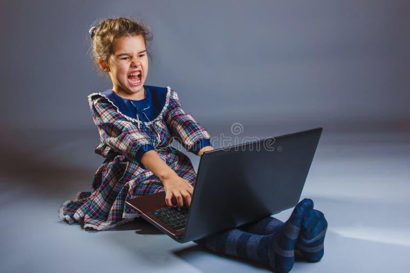 Fille jouant sur l'ordinateur très émotif image libre de droits