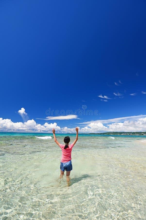 Fille jouant sur la plage photos stock