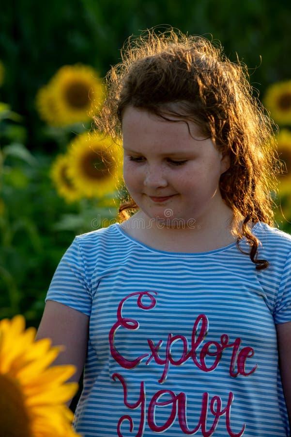 Fille joyeuse de beauté jeune avec le tournesol appréciant la nature et riant sur le gisement de tournesol d'été Sunflare, rayons photographie stock
