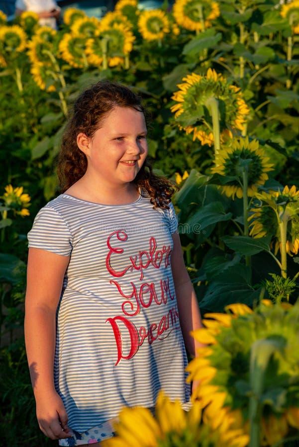 Fille joyeuse de beauté jeune avec le tournesol appréciant la nature et riant sur le gisement de tournesol d'été Sunflare, rayons photographie stock libre de droits