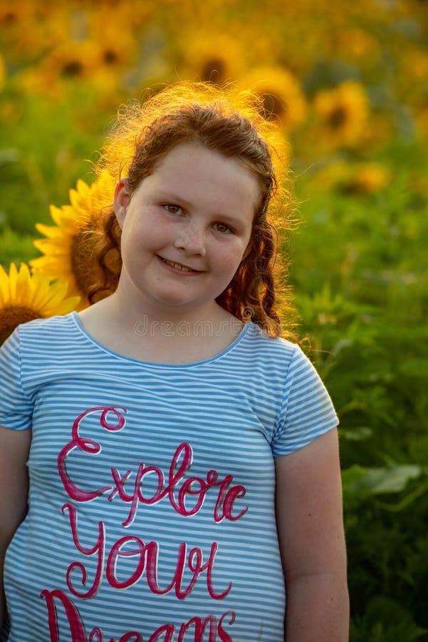 Fille joyeuse de beauté jeune avec le tournesol appréciant la nature et riant sur le gisement de tournesol d'été Sunflare, rayons photos libres de droits