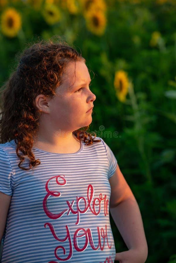 Fille joyeuse de beauté jeune avec le tournesol appréciant la nature et riant sur le gisement de tournesol d'été Sunflare, rayons photos stock