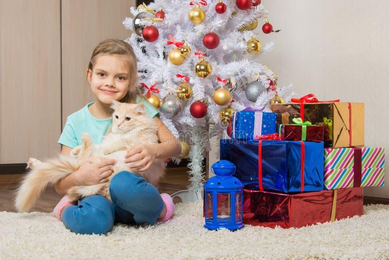 Fille joyeuse de sept ans avec un chat se reposant sous l'arbre de Noël avec des cadeaux photographie stock