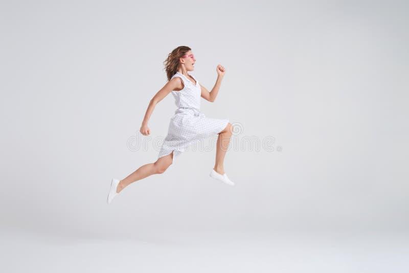 Fille joyeuse folle dans sauter de robe d'été d'isolement au-dessus du backgrou images stock