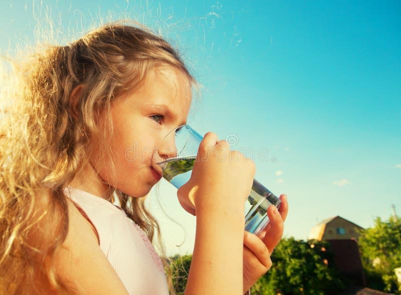 Fille jugeant de verre avec de l'eau images stock