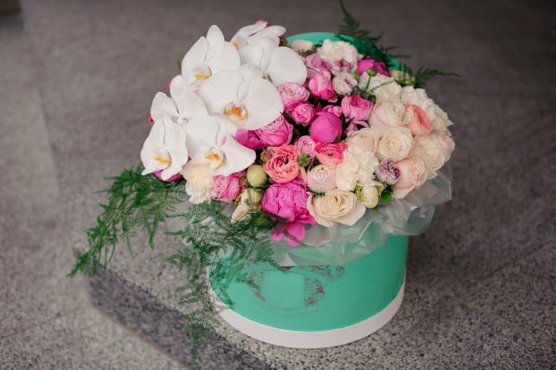 Fille jugeant le beau mélange bouquet blanc et rose de fleur dans la boîte ronde avec le couvercle photo libre de droits