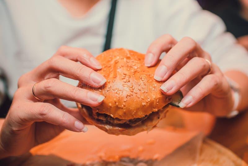 Fille jugeant a mordu outre d'un hamburger de morceau dans une main Fille avec le cheeseburger savoureux délicieux d'aliments de  images stock
