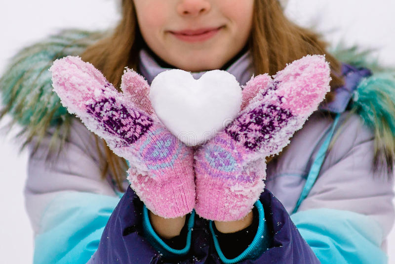 Fille jugeant un coeur fait en neige photos stock