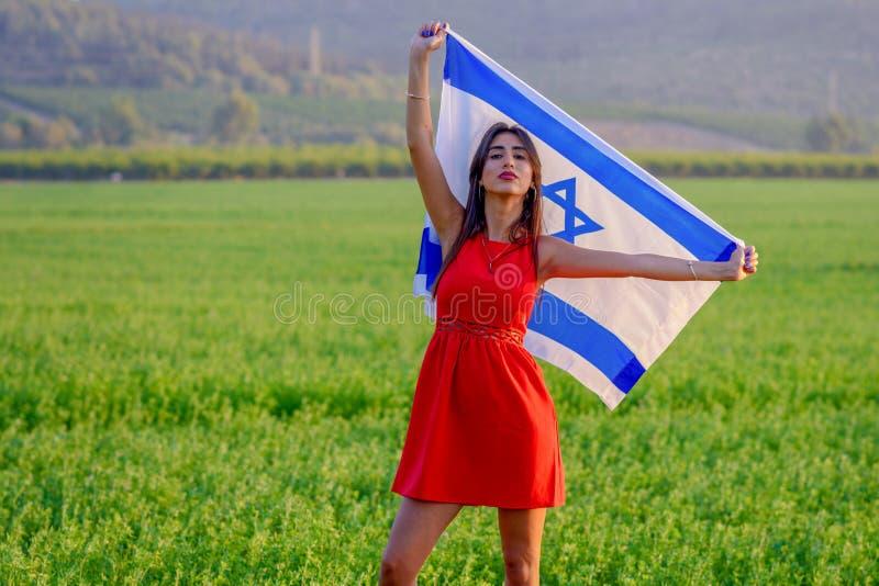 Fille juive avec le drapeau de l'Isra?l sur le paysage stup?fiant en bel ?t? photos stock