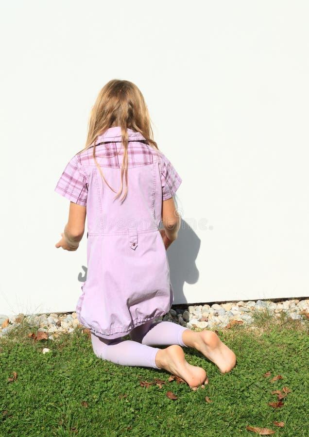 Fille kneeing dans le mur blanc avant images libres de droits