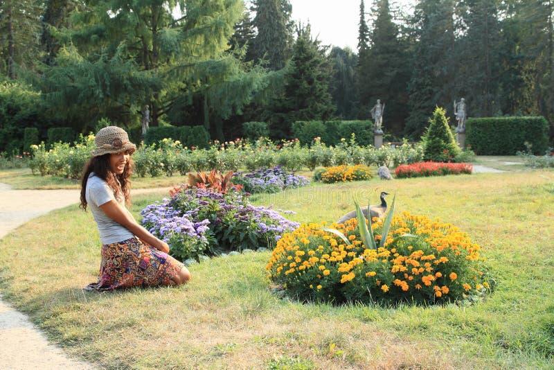 Fille kneeing devant des fleurs images libres de droits