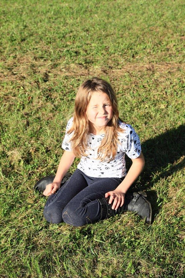Fille kneeing sur l'herbe image libre de droits