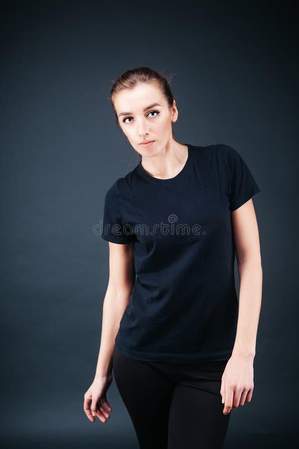 fille ? l'air sportif dans un T-shirt noir et des gu?tres photographie stock