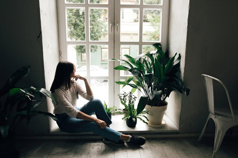 Fille ?l?gante de hippie s'asseyant sur le plancher et regardant la fen?tre rustique blanche avec les plantes vertes en caf? mode photos stock