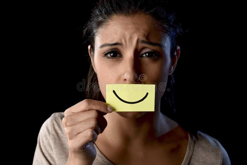 Fille latine déprimée triste latine tenant le papier cachant sa bouche derrière le sourire dessiné par faux images libres de droits