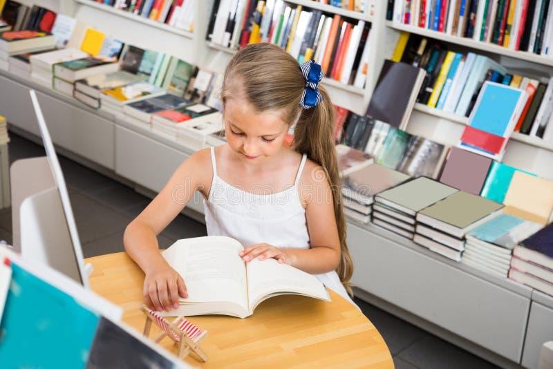 Fille lisant un livre dans la bibliothèque d'école image libre de droits