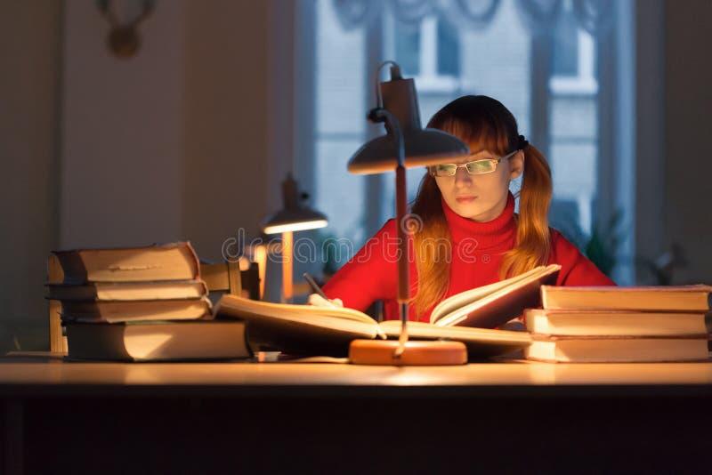 Fille lisant un livre dans la bibliothèque sous la lampe photos libres de droits