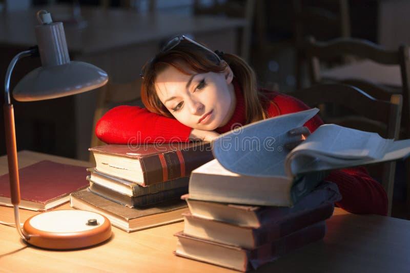 Fille lisant un livre dans la bibliothèque sous la lampe photographie stock libre de droits
