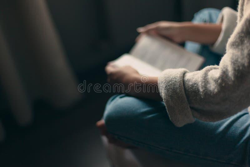 Fille lisant un livre dans la chambre à coucher photographie stock