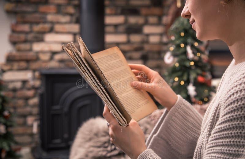 Fille lisant un livre dans une atmosphère à la maison confortable près de la cheminée, plan rapproché images libres de droits