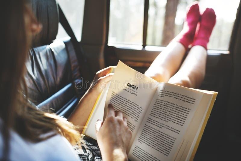 Fille lisant un livre dans une voiture images stock