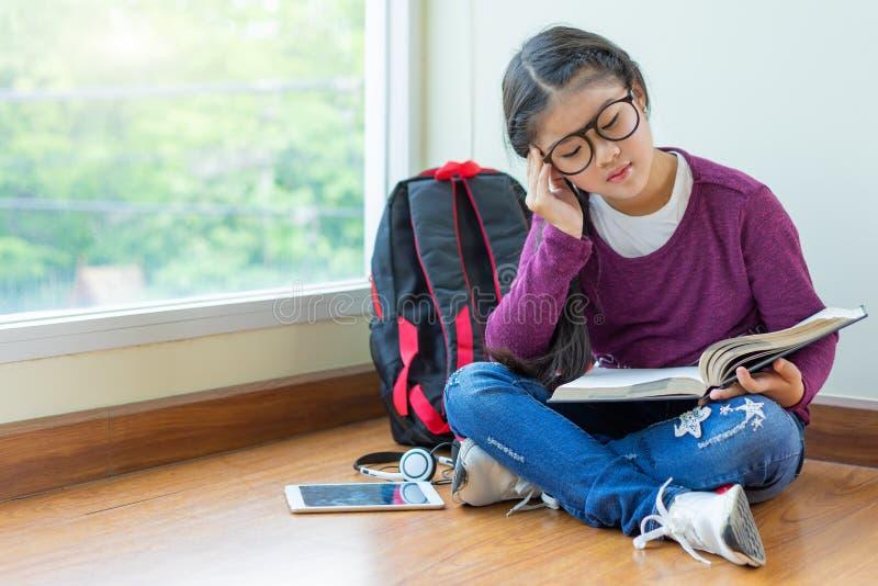 Fille lisant un livre pour l'examen au coin de salle de classe photos libres de droits