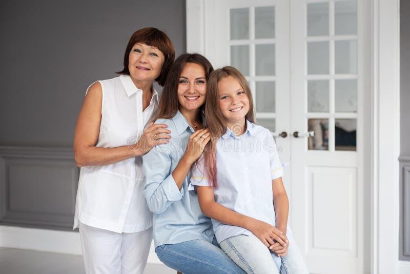 Fille, mère et grand-mère se tiennent les unes à côté des autres et se serrent les coudes photos libres de droits
