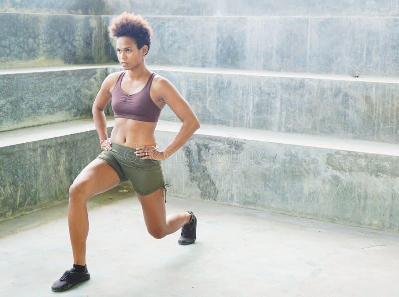 Fille mélanésienne d'athlète d'habitant des îles du Pacifique avec des routines de exercice de exécution Afro image libre de droits