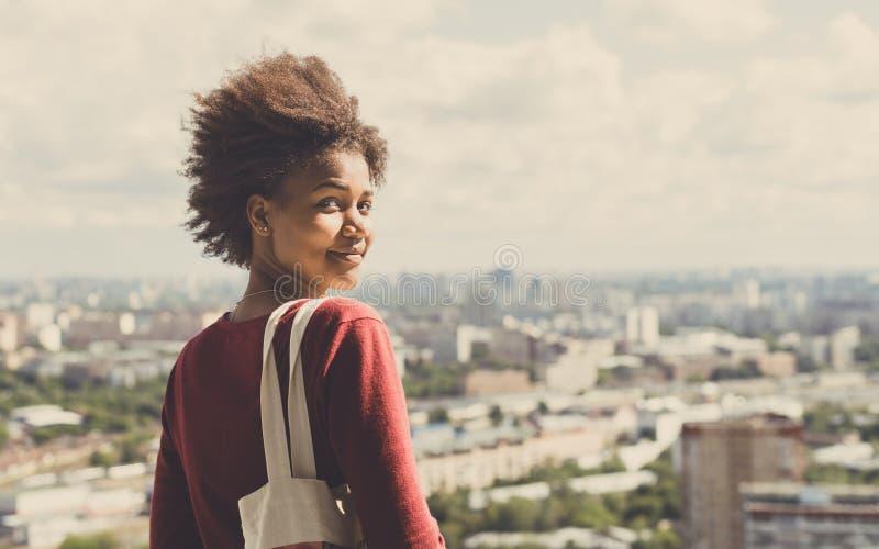 Fille mélangée bouclée sur le balcon avec le paysage urbain derrière photos stock
