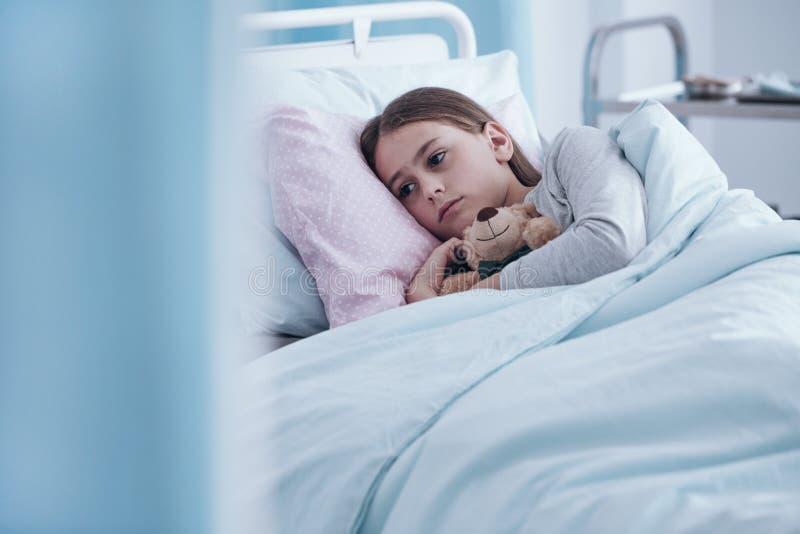Fille malade dans le lit d'hôpital image stock