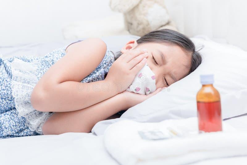 Fille malade se situant dans le lit et l'angine et la toux photos stock