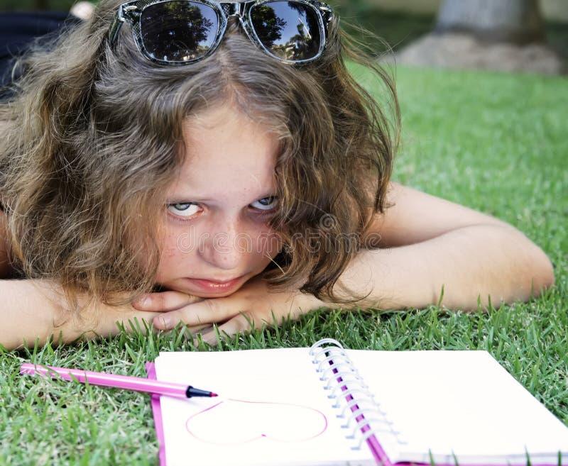 Fille malheureuse se trouvant sur l'herbe avec le cahier images stock
