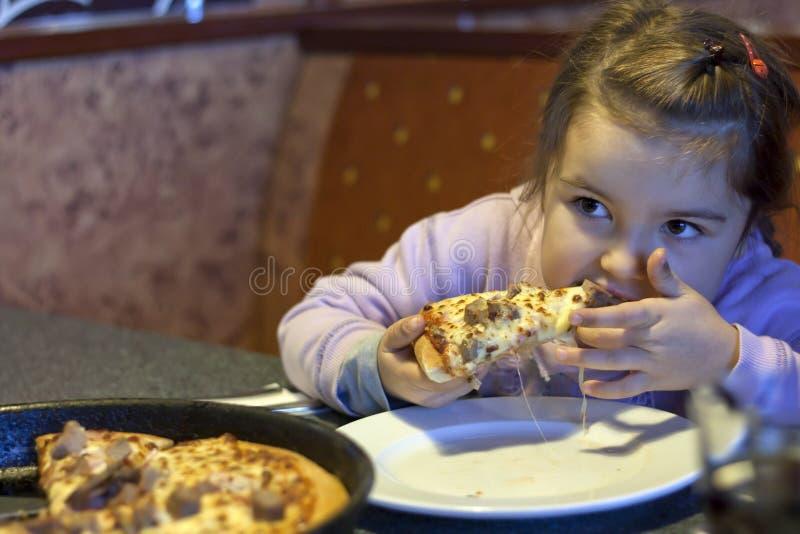 Fille mangeant de la pizza dans le restaurant image stock