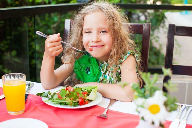 Fille mangeant de la salade à un café photos stock