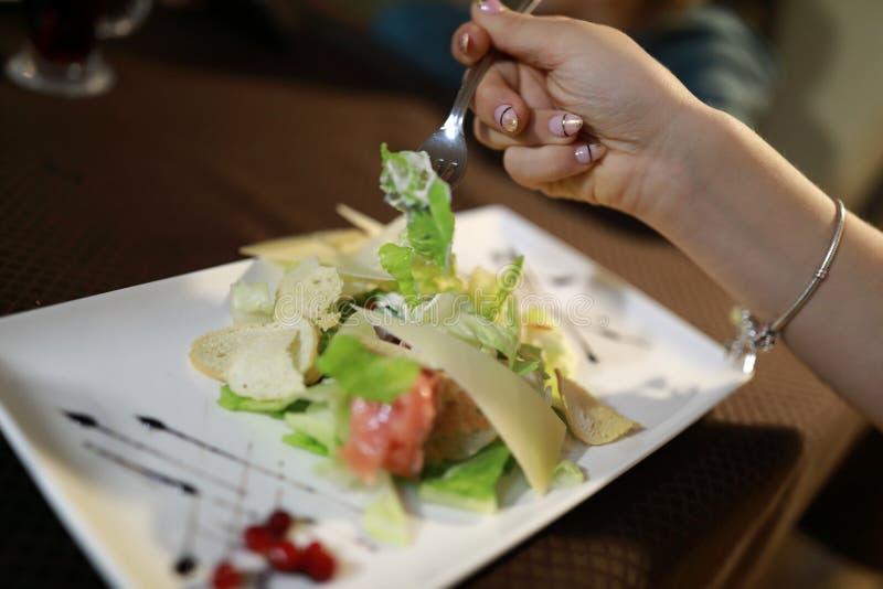 Fille mangeant de la salade de César photographie stock