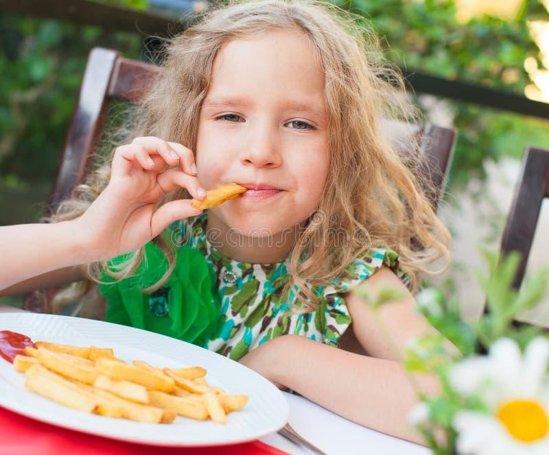 Fille mangeant des pommes chips dans le café photo libre de droits