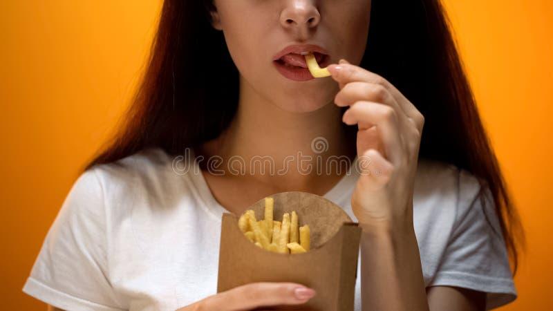 Fille mangeant des pommes frites, appréciant les aliments de préparation rapide, repas énergétique, risque d'obésité photos libres de droits