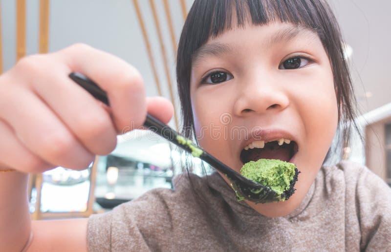 Fille mangeant la crème glacée japonaise de matcha de thé vert photo stock