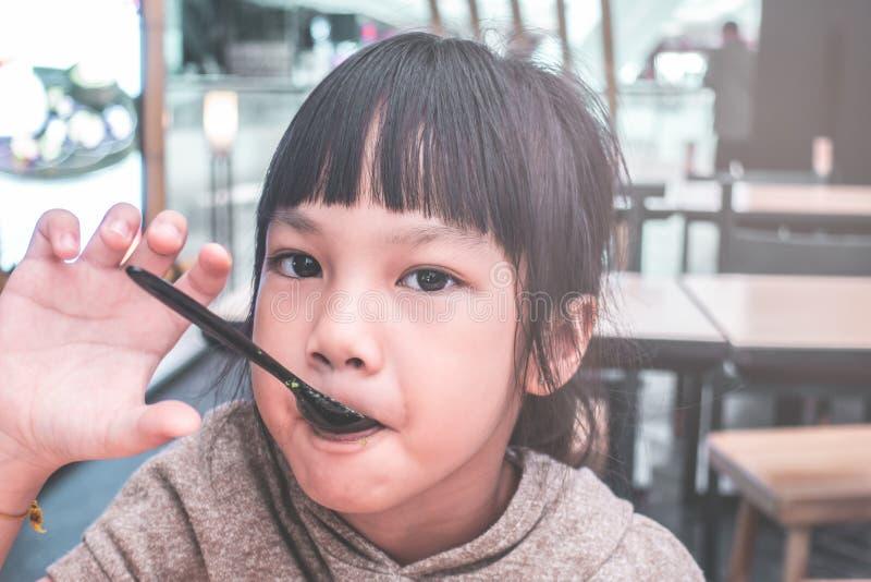 Fille mangeant la crème glacée japonaise de matcha de thé vert photos libres de droits